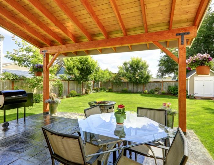 Terrasseüberdachung aus Holz, ein Tischlein aus Glas, Fliesen als Bodenbelag