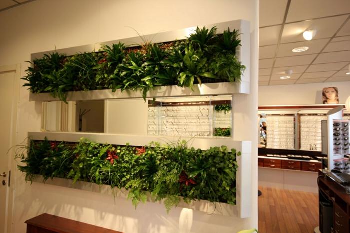 grüne Raumtrennung - Blumentöpfe mit Zimmerpflanzen, die blühen auf weiße Regale