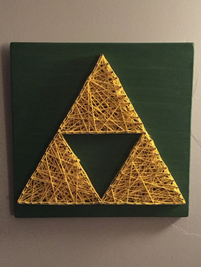 ein grünes Brettchen, eine Fadengrafik Anleitung, drei Dreiecken wie Pyramide