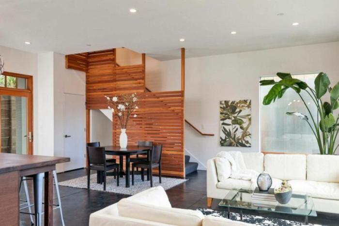 Eine geräumige Wohnung, Treppenhaus Raumteiler Holz neben einem schwarzem Tisch