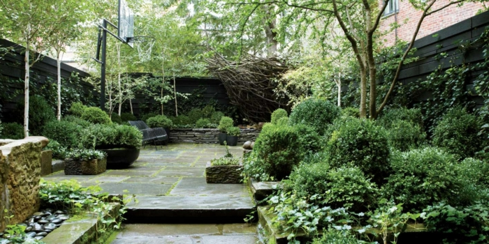 eine Menge grüne Pflanzen, graue Fliesen, hohe Bäume, grauer Sichtschutz, Terrasse bepflanzen