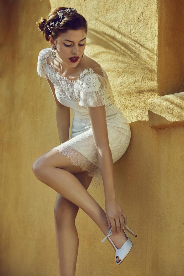 Weißes Spitzenkleid mit kurzen Ärmeln, seitliche Dutt Frisur, weinroter Lippenstift und schwarze Mascara, weiße High Heels