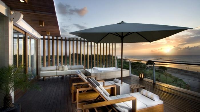 eine wunderbare Terrasse am Strand, zwei weiße Liegestühle mit Sonnenschirm in der Mitte