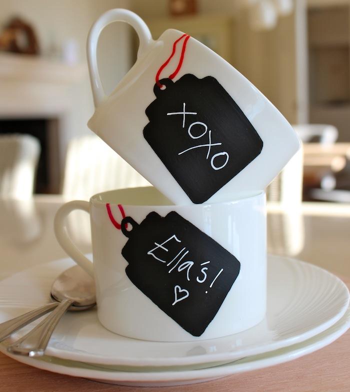 Weiße Tassen selbst verzieren, Anhänger mit schwarzer Farbe aufzeichnen, Küsse und Eigenname