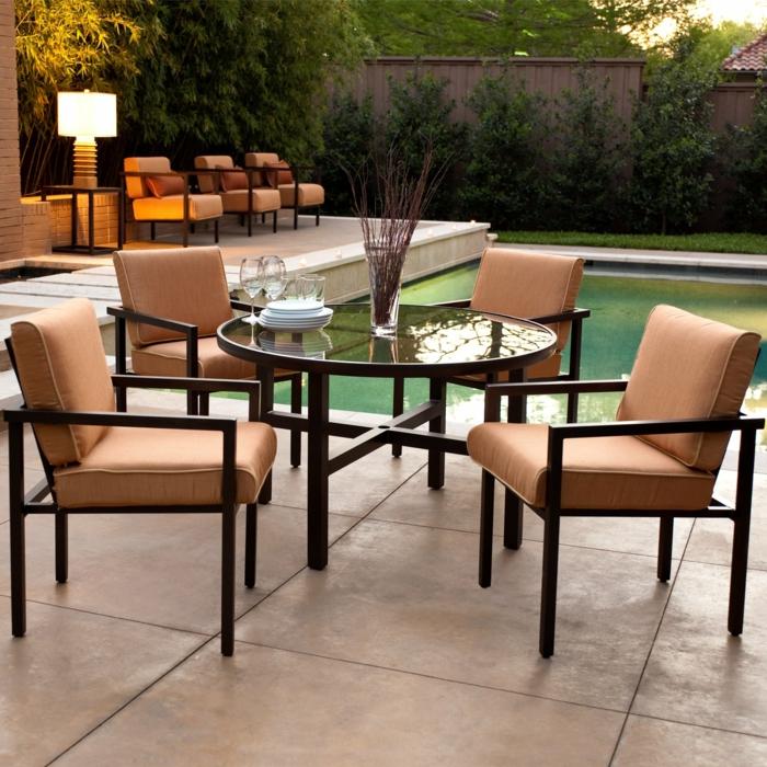 Pflanzen am Zaun, vier Stühle um Glastisch, Terrasse mit Pool, Kübel bepflanzen