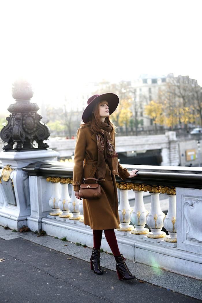 schuckes outfit für frauen, frau mit langem braunem mantel, großem hut und kleiner tasche