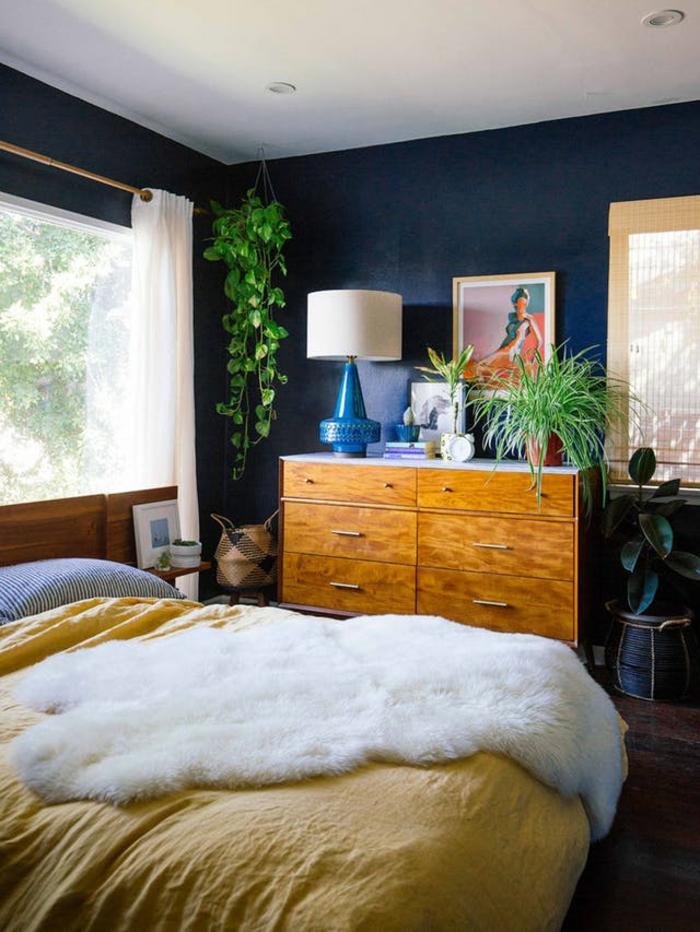 eine grüne Pflanze in der Ecke, ein Bett mit gelber Decke, Regal mit Zimmerpflanzen, moderne Zimmer