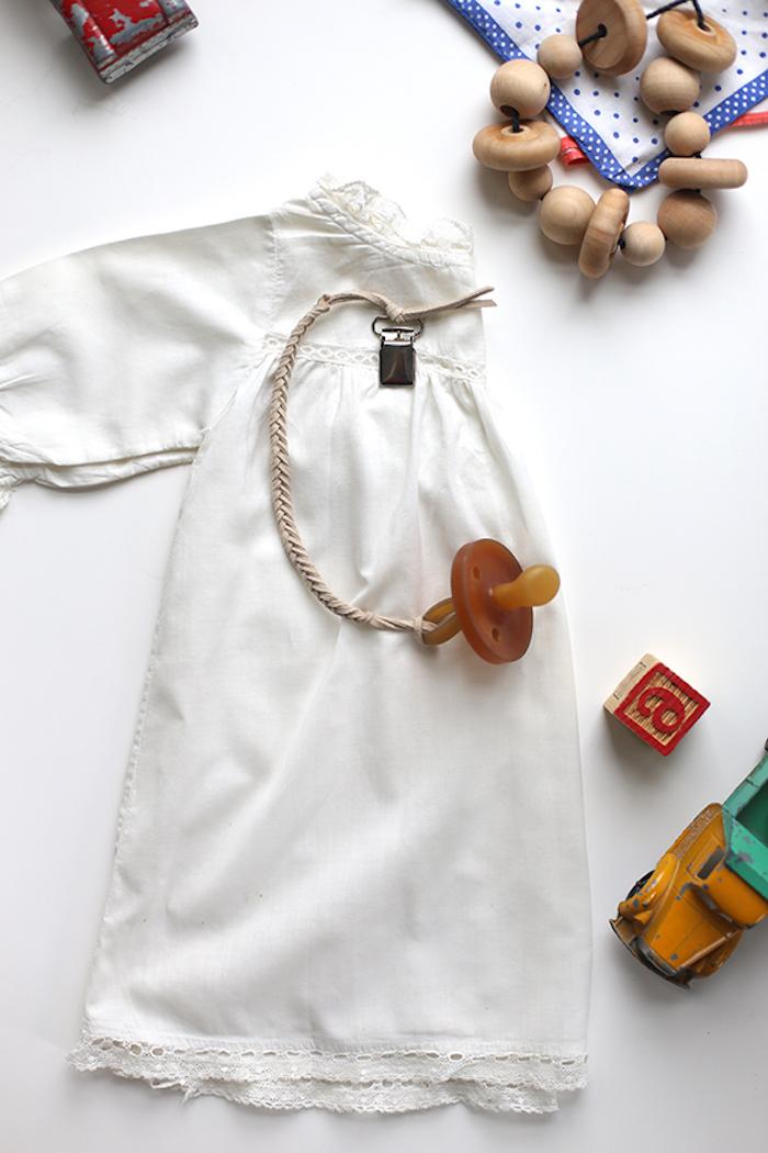 schnuller kette aus beige lederband, weißes babykleid, selbstgemachte schnullerkette
