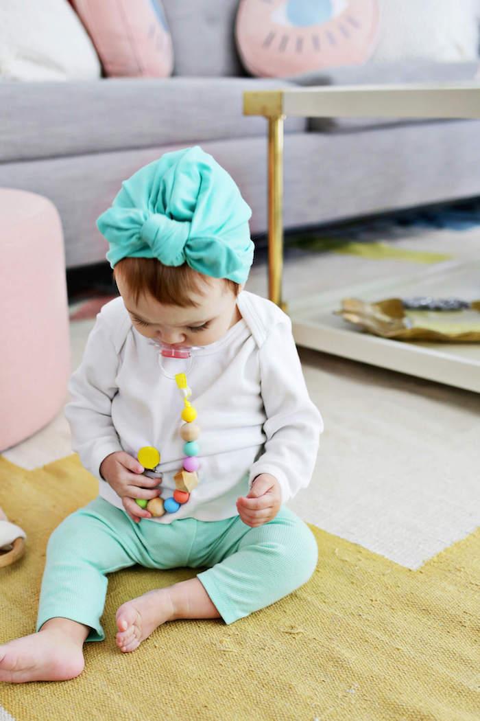 schnullerkette basteln, kleines mädchen mit weißer bluse, minzgrüner hose und bandana