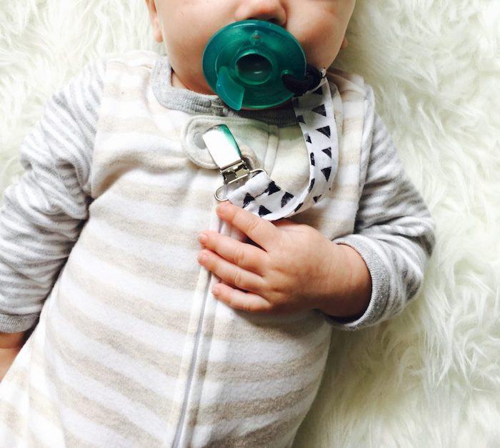 schnullerkette zubehör, kleines baby mit grünem schnuller, schnullerkette aus stoff