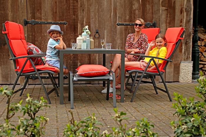 gartenmöbel set für die terrasse schöner tisch mit vier stühlen und einem hocker rote kissen sitzkissen auf den stühlen