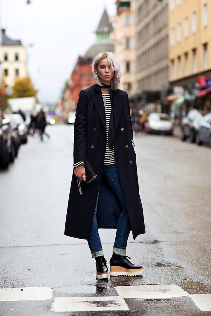schuhtrends hebst winter 2017 18, langer schwarzer mantel, jeans mit getreifter bluse, kurzhaarfrisur, platin-blond
