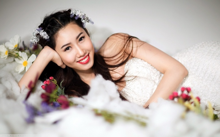 Echte Blumen im Haar, weißes trägerloses Kleid, knallroter Lippenstift und schwarze Mascara