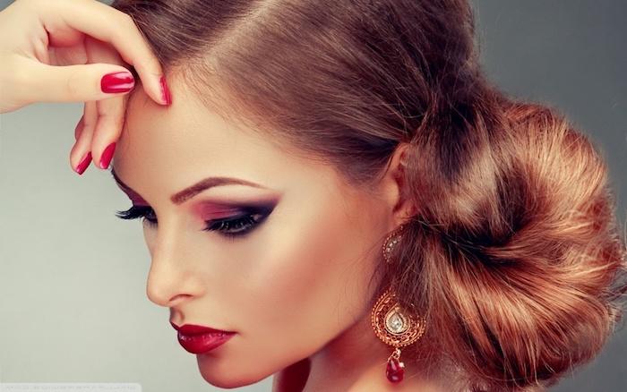 Kastanienbraune lange Haare in Dutt Frisur, Smokey Eyes und roter Lippenstift, goldene Ohrringe mit Kristallen, roter Nagellack