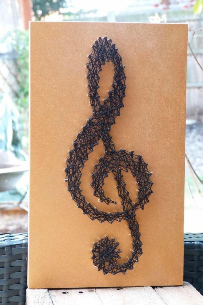 ein Violinschlüssel in schwarzer Farbe, eine orange Tafel, kleine Nagel, die kaum zu sehen sind, Fadengrafik Vorlage