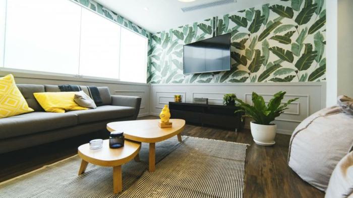 ein graues Sofa, zweiteiliger Couchtisch, eine Wand mit Tapeten in Blättermotiven versehen
