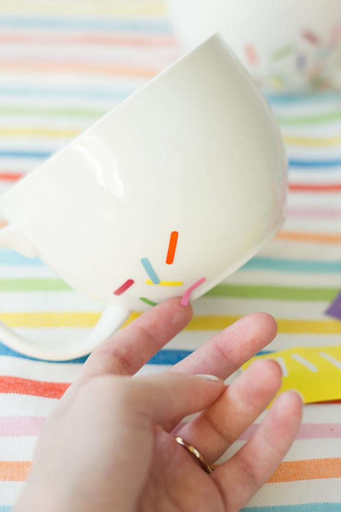 Kleine Streifen aus den Aufkleber ausschneiden und auf die weiße Tasse kleben