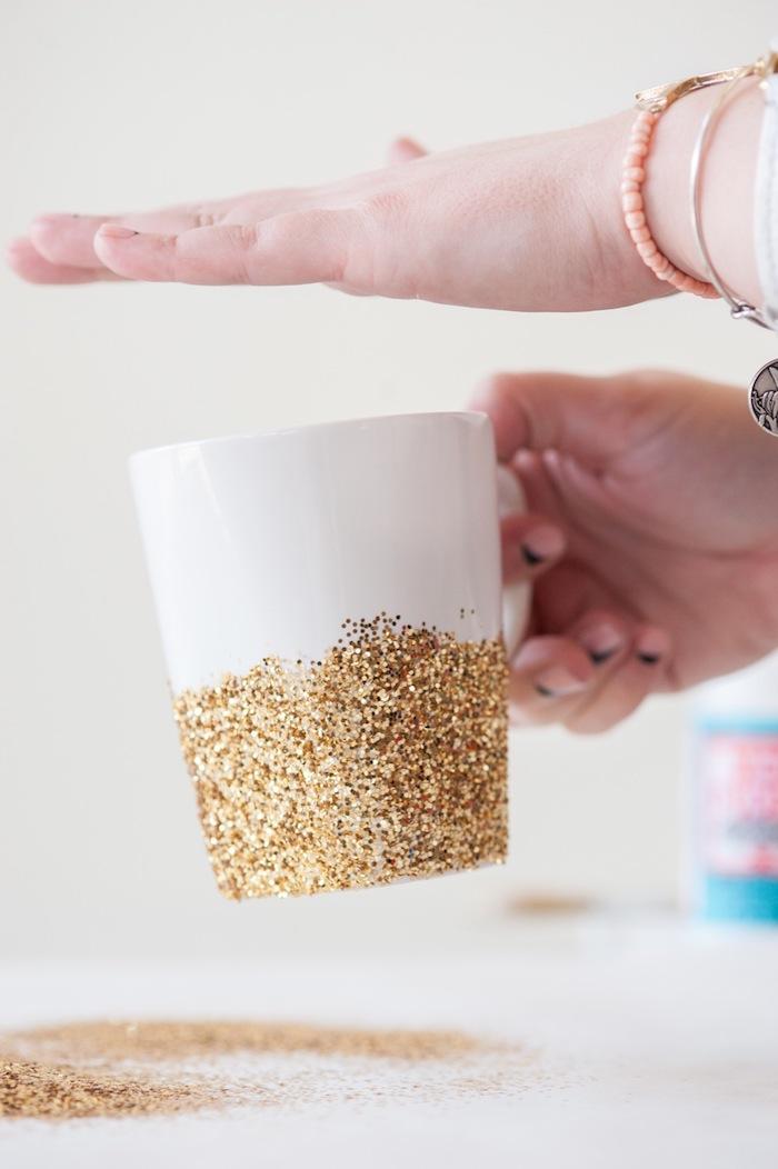 Die funkelnde Tasse ist schon fertig, weiße Porzellantasse mit goldenem Glitzer verziert