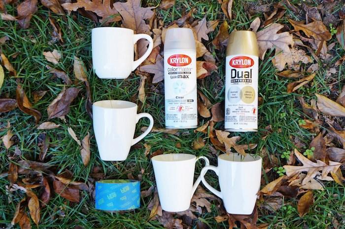 Tassen mit Spray besprühen, dazu brauchen Sie weiße Porzellantassen, goldenen Spray und Klebeband