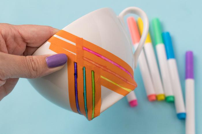 Bunte Streifen mithilfe Klebeband auf eine weiße Tasse aufzeichnen, Permanentmarker benutzen