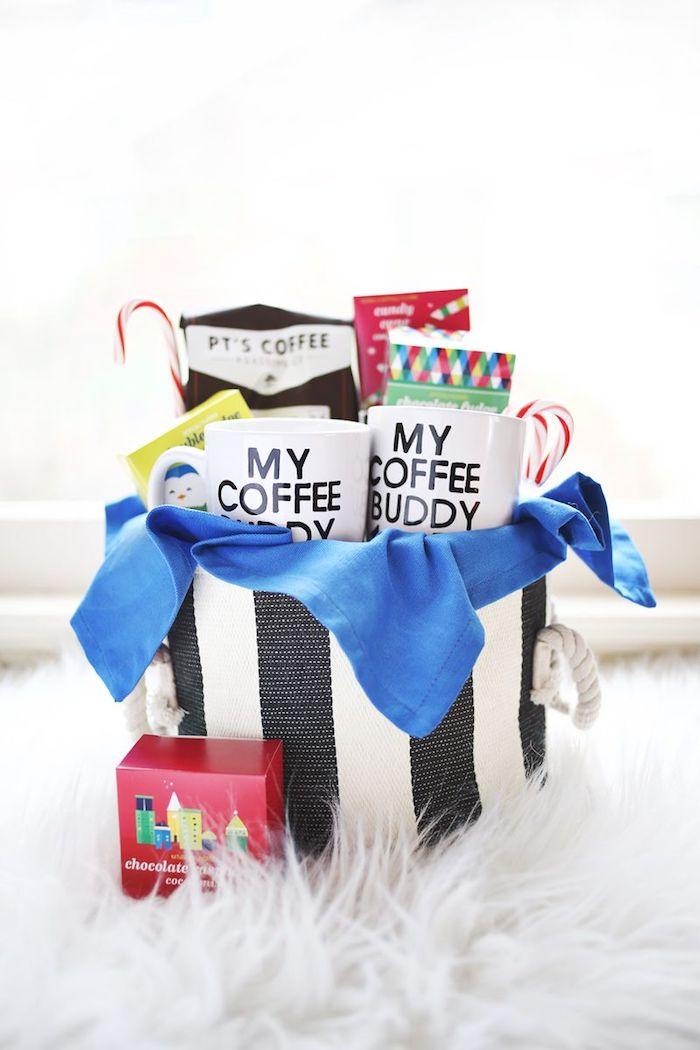 Korb voller Geschenke zu Weihnachten, selbst beschriftete Tassen, schwarze Aufschriften auf weißem Grund, Zuckerstangen und bunte Verpackungen