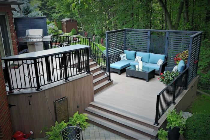 eine Terrasse auf zwei Etagen, blaue Loungemöbel mit weißen Kissen, Terrassen Gestaltungsmöglichkeiten