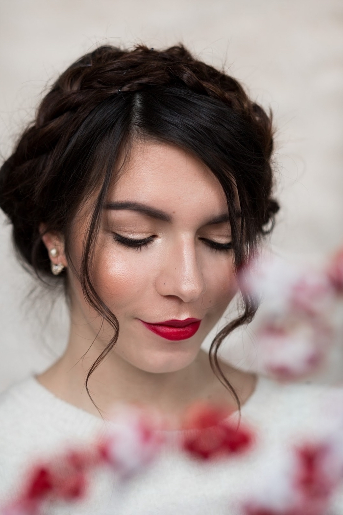eine frau mit festlicher frisur, zwei strähne hängen vor dem gesicht, rote lippen, lippenstift rot
