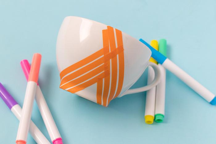 Tassen in fröhlichen Farben selbst gestalten, Streifen aus Klebeband ausschneiden und auf die Tasse aufkleben