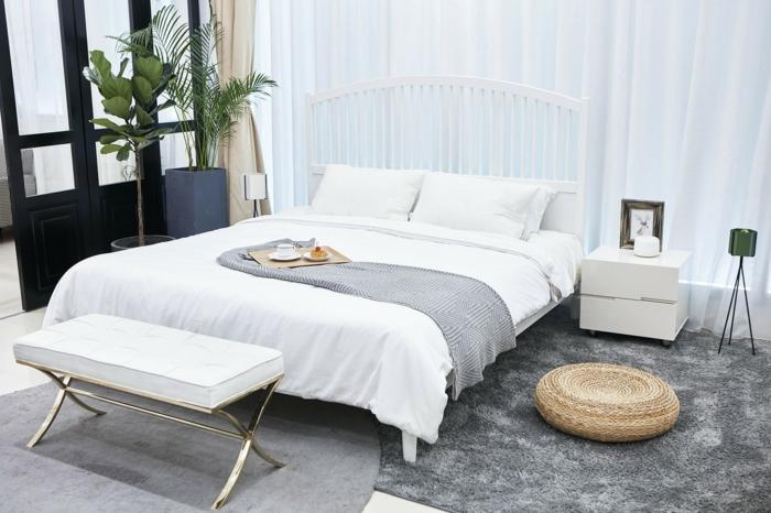 graue Teppiche, ein weißes Bett mit zwei Kissen, zwei Pflanzen in der Ecke, moderne Zimmer