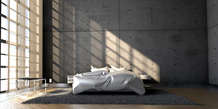 ein graues Schlafzimmer mit Glaswand und weißes Bett, grauer Teppich, viel natürliches Licht