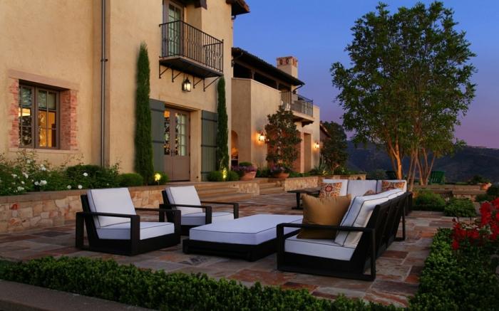 eine geräumige Terrasse mit weißen Sessel und Tisch, von Gras umgeben, Terrasse planen