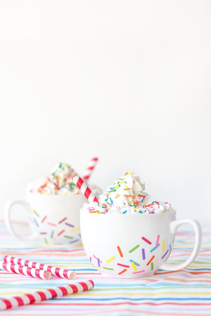 Weiße Porzellantassen mit bunten Zuckerstreuseln, heiße Schokolade mit Sahne genießen