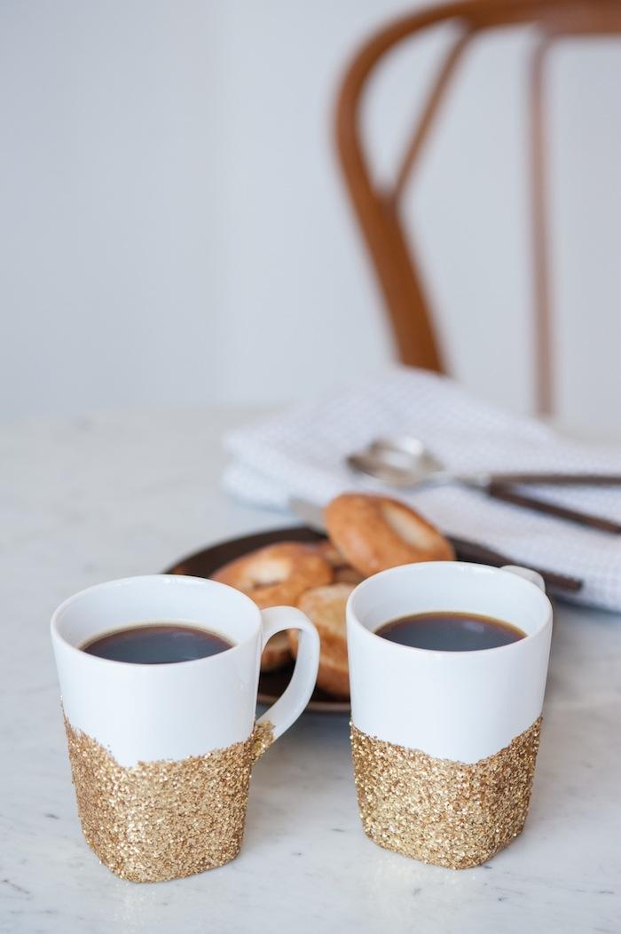 Weiße Tassen mit goldenem Glitzer verziert, Kaffee und Donuts genießen