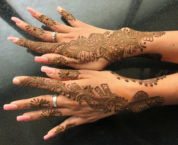 wie lange hält henna, frau mit sehr detallierten tätowierungen mit henna, mehndi, lange nägel