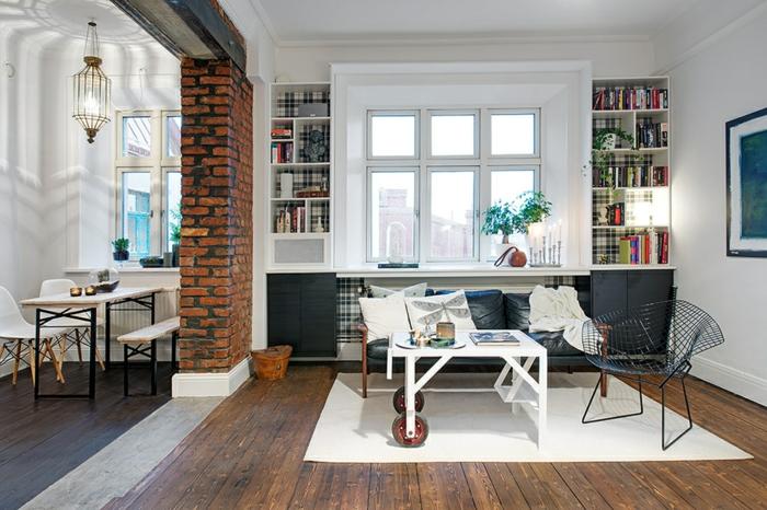 ein helles Wohnzimmer mit zwei Regalen und Ledersofa wird durch Backstein Raumteiler Trennwand von dem Esszimmer getrennt