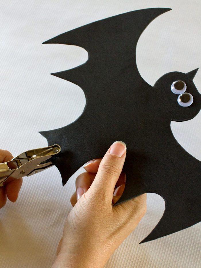 basteln mit kindern, zwei hände und eine große schwarze selbstgebastelte fledermaus aus papier und mit zwei schwarzen flügeln und schwarzen augen