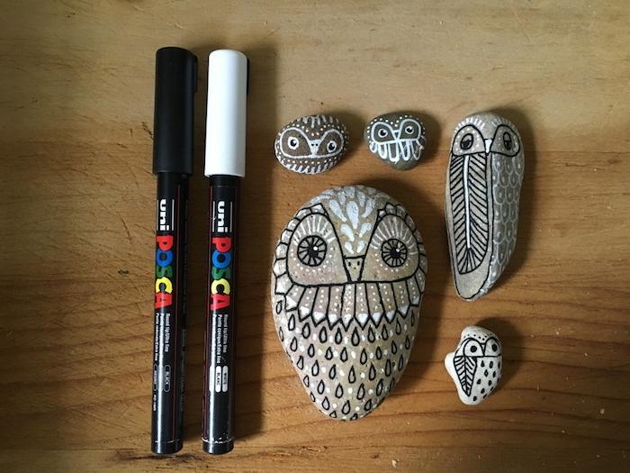 fünf kleine bemalte steine, kleine eulen mit weißen und schwarzen federn, tisch aus holz