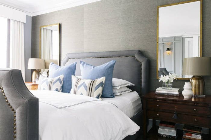 ein Bett in grauer Farbe mit blauen Kissen, zwei Spiegel und zwei Regale, zwei Lampen