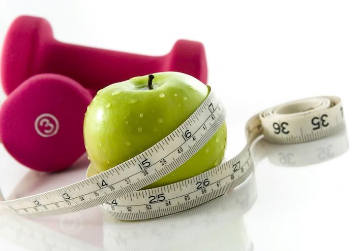 schnelles frühstück, grüner apfel, metermaß, rosa halteln, weißer boden, gewicht verlieren, abnehmen