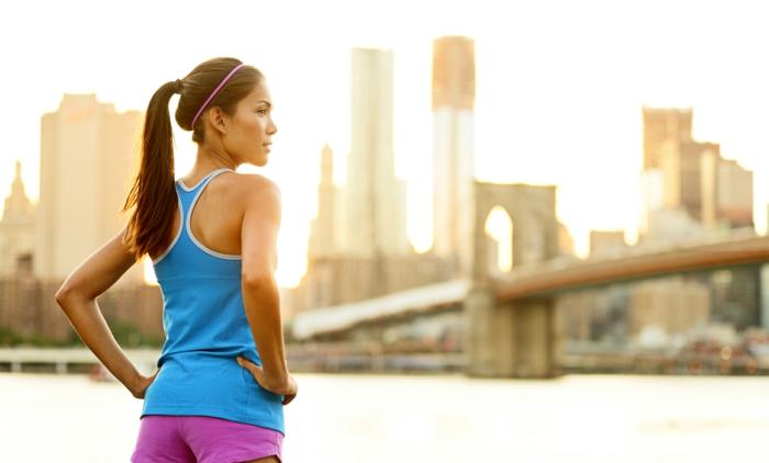 gesund abnehmen mit viel bewegung eine schlanke dame hält ihre figur fit indem sie morgens laufen geht gebundene haare sportanzug