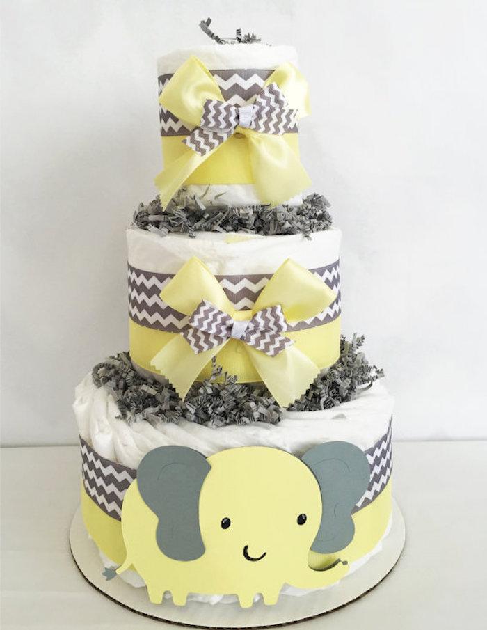 eine große torte ais vielen weißen windeln und mit einem gelben elefanten mit grauen ohren und gelben schleifen, eine windeltorte selber machen