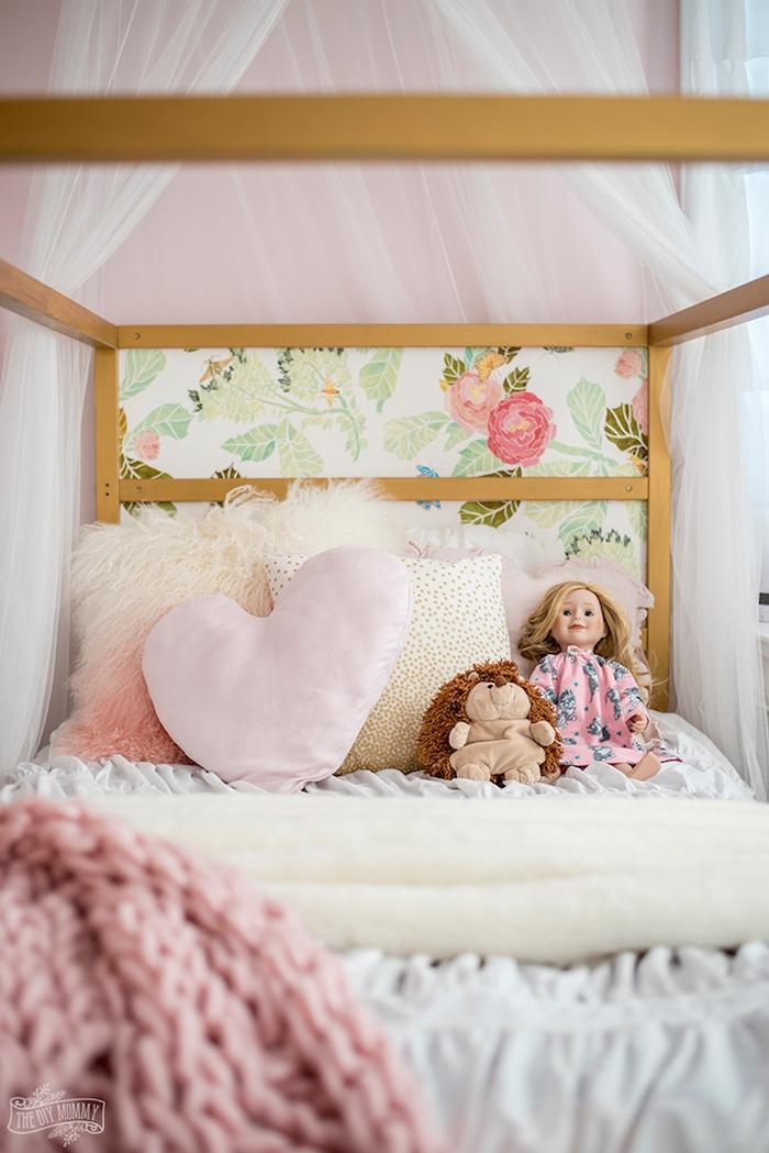 Babybett in Rosa mit Blumenmuster, Puppe mit blonden Haaren und Kuscheltier Igel, Herzkissen und kuschelige Decke