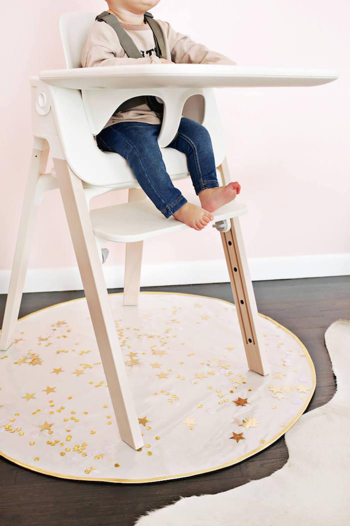 Weißer Hochstuhl für Babys, Baby mit rosa bluse und Jeans, goldene Sternchen