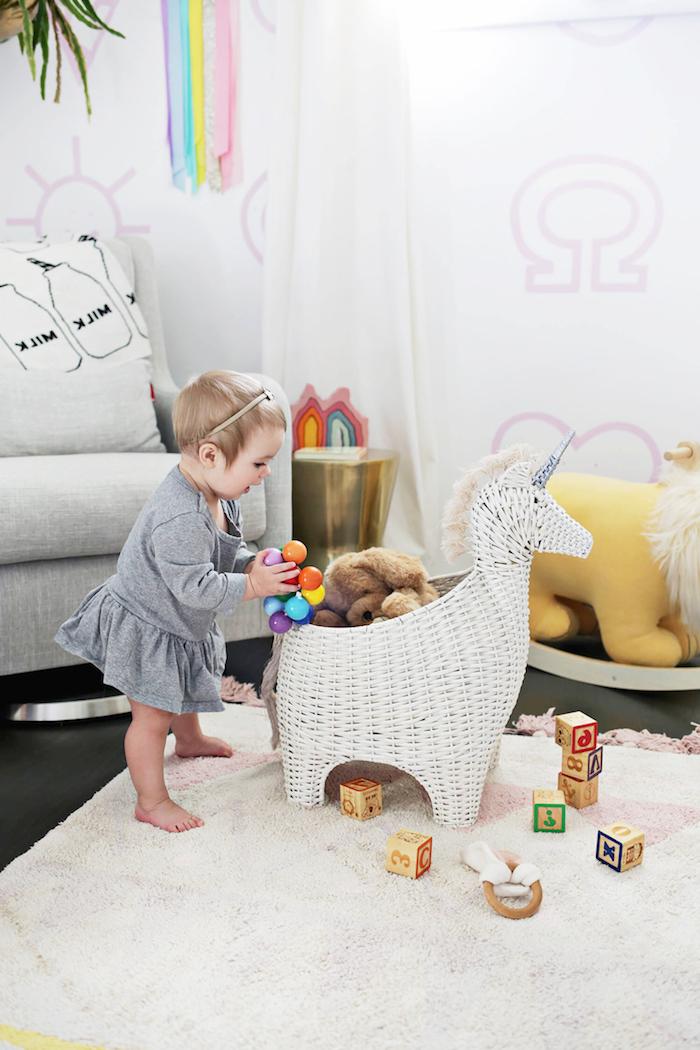 Babyzimmer Einrichtung, süßes Baby mit grauem Kleid, Kuscheltiere und Spielzeuge aus Holz, Einhorn aus Rattan