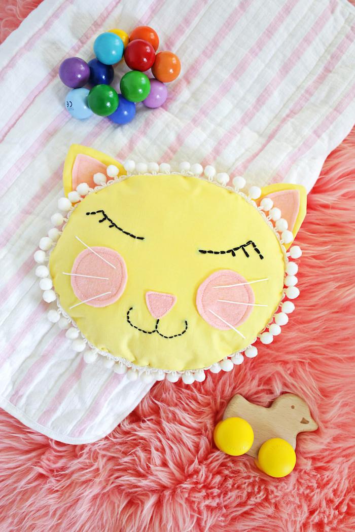 Süßes Kissen fürs Babyzimmer, gelbe Katze, rosa Wangen und Ohren, mit weißen Pompons verziert