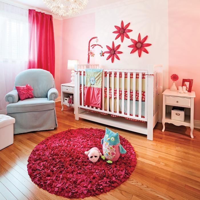 Babyzimmer Deko, roter Teppich und Papierblumen an der Wand, weißes Babybett und blauer Sessel