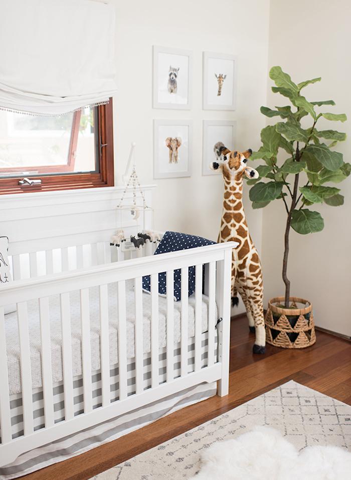 Babyzimmer in Weiß, Kuscheltier Giraffe neben dem Babybett, grüne Pflanze