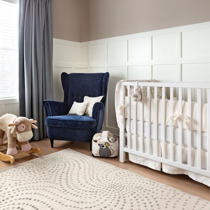 Babyzimmer Einrichtung, dunkelgrüner Sessel, weißes Babybett, Korb mit Maus, Kuscheltier Kuh