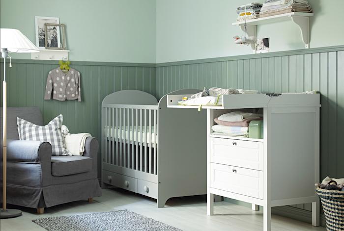 Babyzimmer in Grün, grauer Sessel, weße Möbel, weiße Stehlampe, Bilder an der Wand