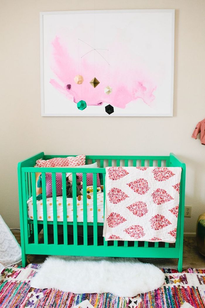 Grpnes Babybett, Mobile als Edelsteine, bunter Teppich, viele kleine Kissen im Bett